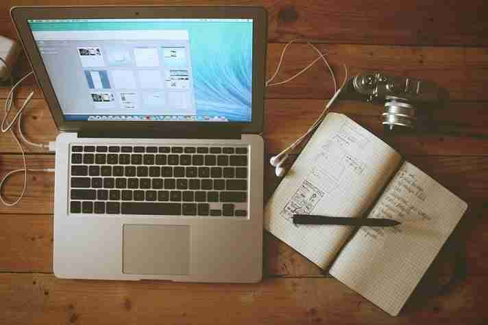 Laptop on Desk with Open Journal